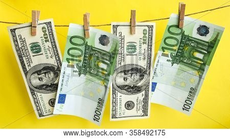 100 Dollars And Euros On A Rope, Dollars With A Clothespin On A Rope Isolated On A Yellow Background