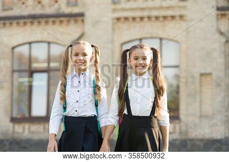 Lucky To Meet Each Other. Cheerful Smart Schoolgirls. Happy Schoolgirls Outdoors. Small Schoolgirls