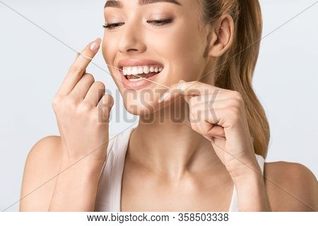 Toothcare Routine. Happy Young Lady Flossing Teeth Over Gray Background In Studio. Cropped