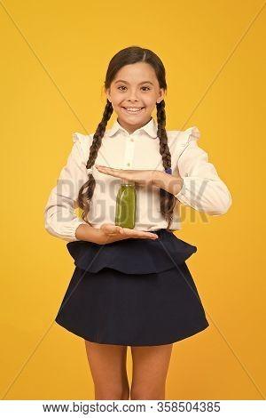 Keeping You Energetic. Happy Energetic Schoolchild Holding Juice Bottle On Yellow Background. Little