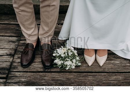 Legs Of Newlyweds On Wooden Background. Stylish Shoes Of Bride And Groom Outdoors. Bridal Bouquet On