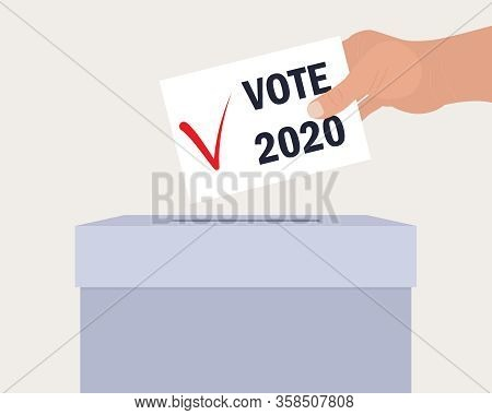 Voting Concept. A Human Hand Puts An Envelope In A Ballot Box. On Paper Checkmark And Text Vote 2020