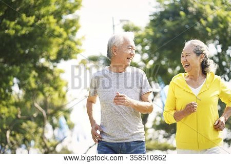 Happy Asian Old Couple Jogging Running Outdoors In Park