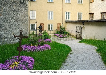 Pathway Inside The Old Nonnberg Abbey In Salzburg, Austria, With Flowers And Grave Markers