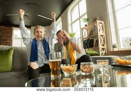 Excited Family Watching Football, Sport Match At Home. Beautiful Caucasian Couple Cheering For Natio