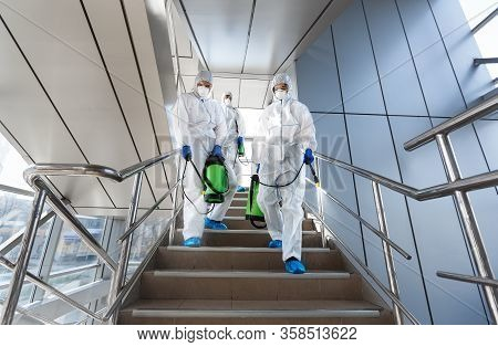Government Workers In Protective Suits Making Disinfection Of Stairs And Surfaces From Coronavirus,