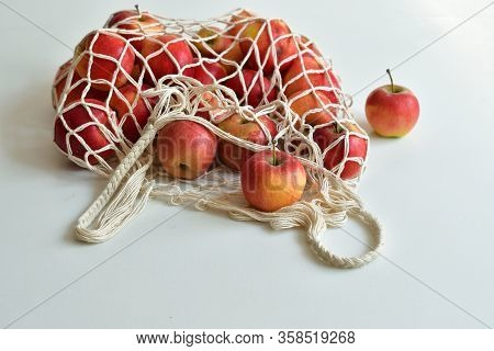 Mesh Textile Bag Full Of Red Apples. .zero Waste Food Shopping. Eco Natural Bags On White Background