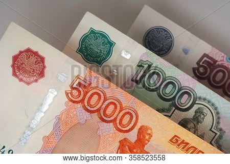 Fragments Of Russian Banknotes Close-up. 5000, 1000 And 500 Rubles Bills Hang In The Air Over A Gray