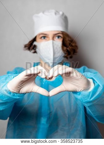 Medical Worker In A Disposable Mask And A Lab Coat Makes A Heart Sign. Gray Homogeneous Background.