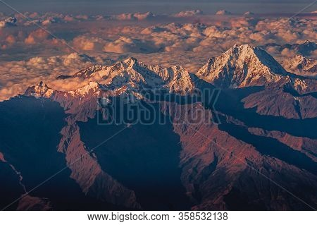 Viewed From Above The Andes Mountains In Clouds And Snow At Their Top At Sunset