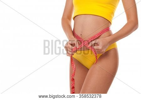 Tanned woman with measure tape isolated on white background. Close up of sporty and beautiful female body. Healthy lifestyle, dieting, fitness, weight loss concept