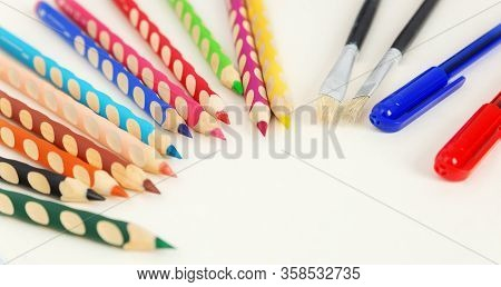 Colored Pencils, Pens And Brushes On A White Background With Copy Space. Selected Focus.  Ergonomic