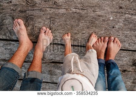 Bare Feet Of Family. Wooden Bridge. Mom, Dad And Baby Walk Bare Feet On The Wooden Bridge. Happy You