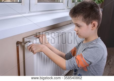 School-age Boy Holds The Temperature Control Knob On The Radiator And Sets The Right Temperature.