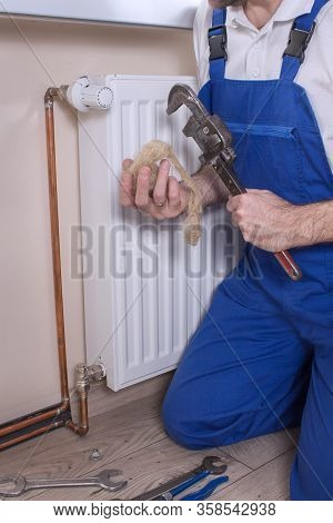 A Plumber Holds An Adjustable Wrench In One Hand And A Tow In The Other. In The Background A Wall Wi