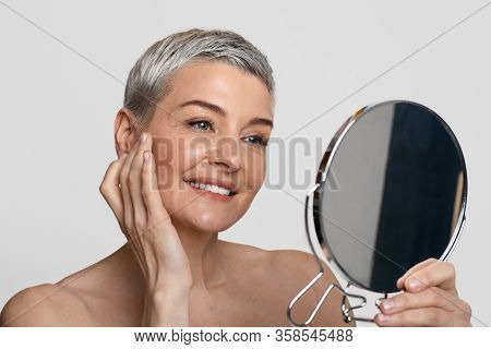 Skincare For Middle-aged Women. Beautiful Mature Lady Looking At Mirror And Applying Anti-aging Crea