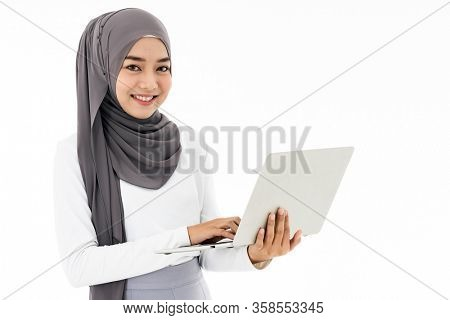 Asian young adult woman wearing hijab using laptop work from home to search and doing office work standing on white background - office, business, finance and work station concept