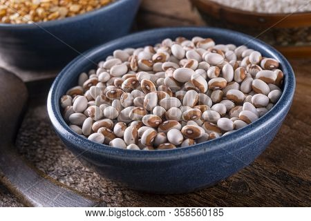 A Bowl Of Dried Yellow Eye Beans On A Rustic Wood Table Top.