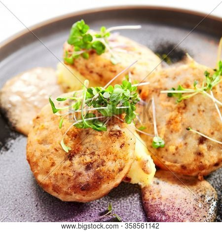 Fishcakes with garden cress closeup view. Delicious filleted fish with greenery on tray. Croquette seafood with aromatic sauce. Restaurant dish, culinary presentation. Food composition