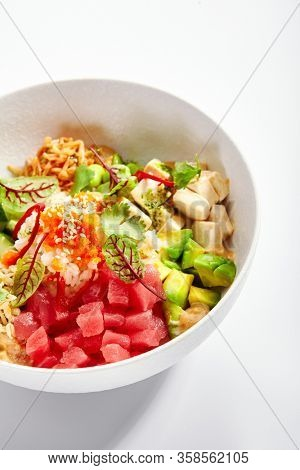 Poke with tuna and noodles. Hawaiian salad with avocado and tofu closeup view. Traditional polynesian dish with rice and cheese. Delicious native cuisine.