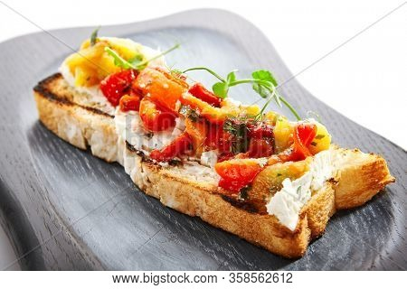 Delicious bruschetta with baked peppers close up view. Tasty roasted bread with cheese and vegetables. Traditional italian antipasto with greenery on wooden tray. European cuisine, food composition