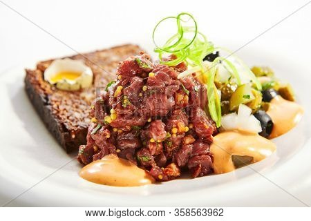 Beef tartare closeup view. Delicious chopped meat with sauce and bread. Dish with mustard and greenery on plate. Restaurant delicacy, haute cuisine. Food presentation, traditional recipe