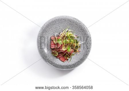 Tataki tuna top view. Traditional japanese culinary method. Delicious fish on plate. Tasty sliced seafood with greenery and seasonings. Asian cuisine, food composition. Restaurant dish