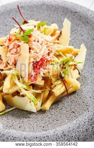 Pasta with crab, zucchini and truffle cheese. Delicious italian meal closeup view. Tasty dish with seafood and aromatic greenery on plate. European cuisine, restaurant food composition