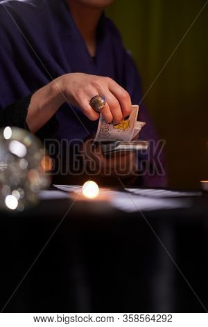 12.02.20. Moscow, Russia. Fortune teller woman in blue dress divines on cards sitting at table with candles .