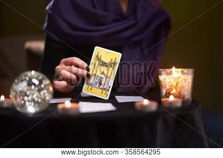 12.02.20. Moscow, Russia. Close-up of fortuneteller's hands with tarot card at table with candles, magic ball