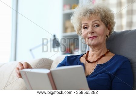 Elderly Woman Self-isolation Reading Book At Home. Coronavirus Pandemic Conditions. Effective Way To