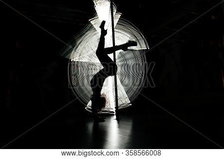 Silhouetted Of A Young Sexy Girl On A Pylon In The Dark With A Beautiful Picture Of Light