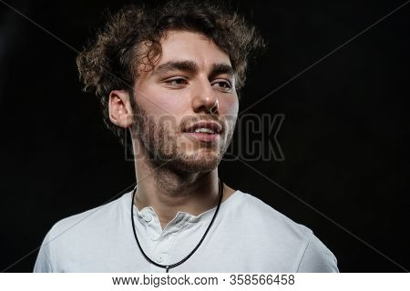 Curly And Hansome Caucasian Man Standing In A Dark Studio On A Grey Background, Wearing Casual White