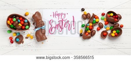 Chocolate easter eggs, choco rabbit and colorful sweets on wooden background greeting card. Top view. Flat lay with greetings
