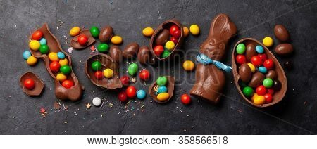 Chocolate easter eggs, choco rabbit and colorful sweets on stone background greeting card. Top view. Flat lay