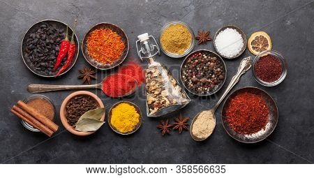 Various spices in bowls and spoons on dark stone table. Indian cuisine. Top view flat lay