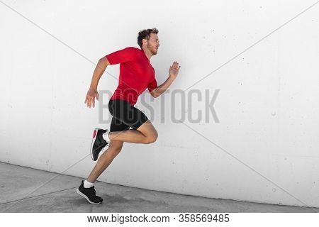 Running man jogging fast profile sideways against white wall outdoor background. Male athlete training healthy active lifestyle.