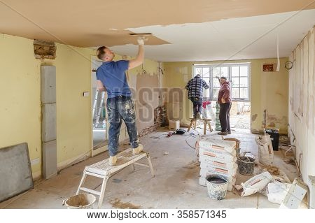 Buckingham, Uk - March 14, 2016. Team Of Builders Working On A Home Interior Renovation With A Plast