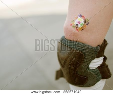 Close Up Of Caucasian Leg With Kneecap For Protection. Colorful Patch On Top Of Leg. Roller Skating