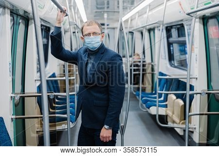 Coronavirus Crisis In 2020. Man Commutes To Work In Empty Underground, Uses Public Transport, Uses P
