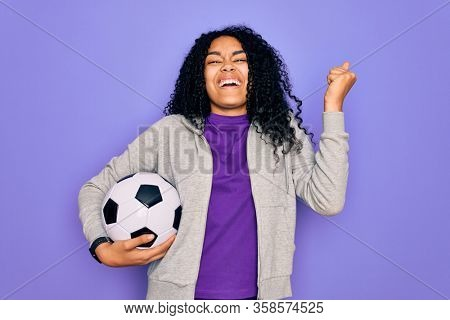 African american curly player woman playing soccer holding football bal over purple background screaming proud and celebrating victory and success very excited, cheering emotion