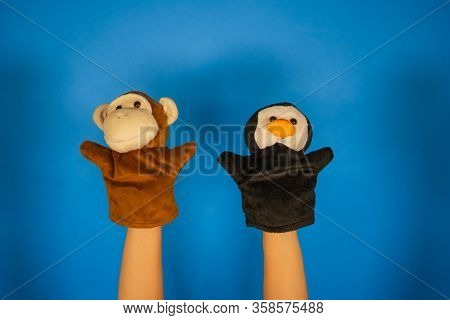 Soft Puppet Toys On Hands On Blue Background. Concept Of Puppet Show. Close-up Of Hands With Puppet
