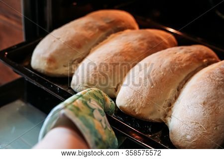 Taking Freshly Baked Homemade Bread Loafs Out Of The Oven With Oven Glove. Homemade Cooking