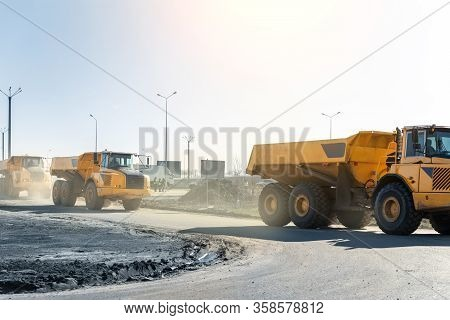 Many Big Articulated Heavy Industrial Yellow Dumper Trucks Driving On New Highway Road Construction