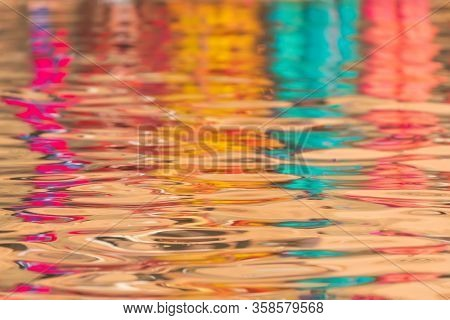 Reflection of indian colorful traditional dresses over the Ganga river water.