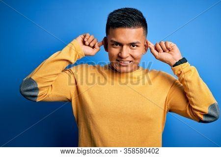 Young handsome latin man wearing yellow casual sweater over isolated blue background Smiling pulling ears with fingers, funny gesture. Audition problem