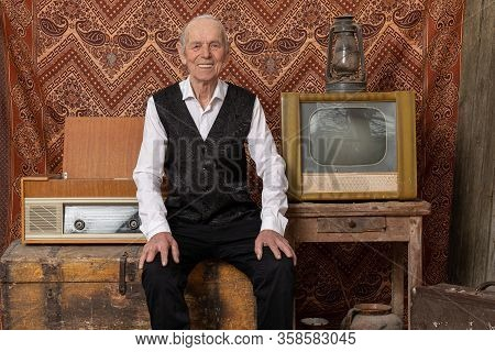 Happy Old Man In Elegant Clothes Sitting On The Aged Chest Near Retro Tv, Radio And Old Gas Llamp, S
