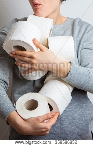 Greedy Woman Holds An Armful Of Toilet Rolls. Panic. Stocks During The Quarantine Period Of The Coro