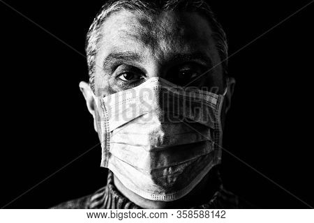 Man with surgical mask. Pandemic or epidemic and scary, fear or danger concept. Protection for biohazard like COVID-19 aka Coronavirus. Close-up  portrait. Black Background. Black and White.