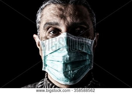 Man with surgical mask. Pandemic or epidemic and scary, fear or danger concept. Protection for biohazard like COVID-19 aka Coronavirus. Close-up  portrait. Black Background.